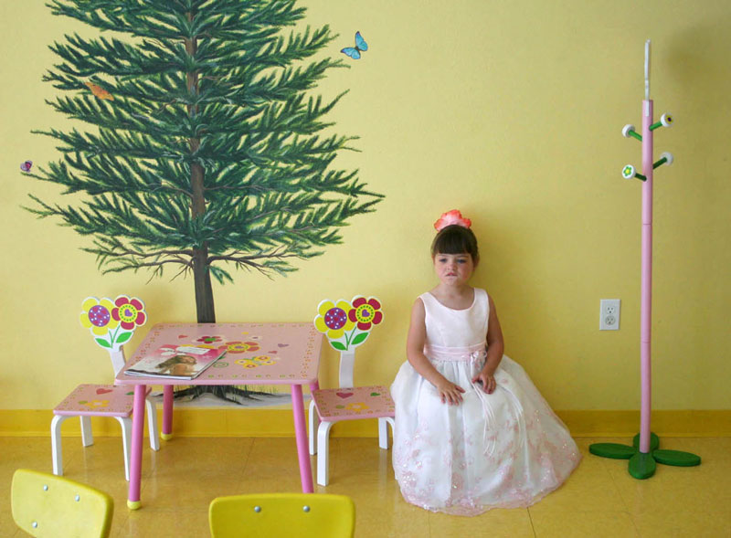 Kiristen, 5, sits in a party dress at Wiggly Fun's tearoom. Wiggly Fun provides children with toys and playrooms, as well as costumes for their imaginations.