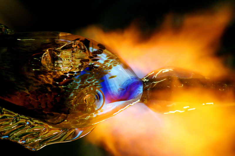 Fire heats a blown glass fish sculpture at Hot Glass Works.