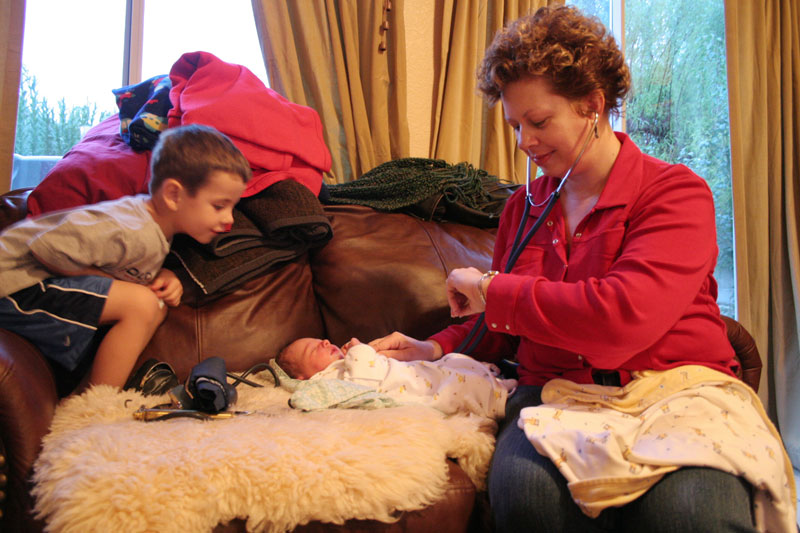 Gunnar watches as Jill takes the heartbeat and pulse of one-day-old Maxelyn in the Mayer's Henderson home Wednesday, Jan. 26, 2005. Colin makes a routine 24-48 hr. postpartum check-up on her patients and their newborns
