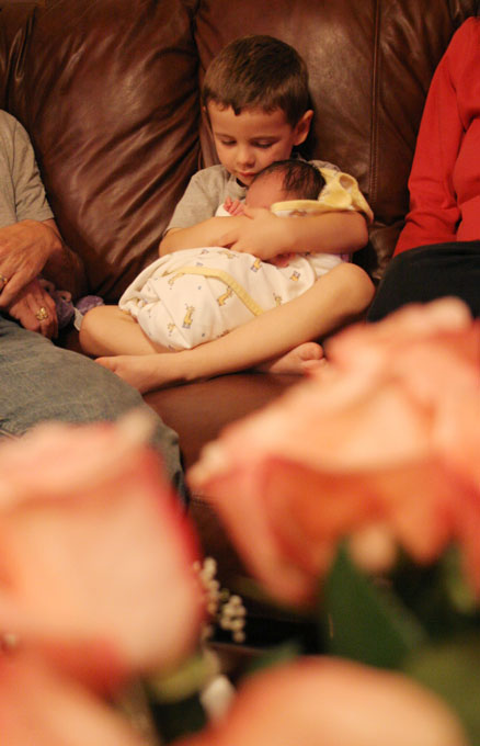 Big Brother Gunnar holds his newborn baby sister for the first time in the family's home Wednesday, Jan. 26, 2005. The family displayed pink roses. The flowers, along with other arrangements, were found that morning on the Mayer's front porch