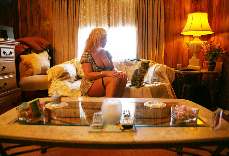 Alicia, who makes a living as a prostitute at the Chicken Ranch brothel, sits in her bedroom with the house cat Meow-Meow at the historic Chicken Ranch brothel Thursday, April 10, 2008, in Pahrump, Nevada. Alicia, who has been with Chicken Ranch off and on for 10 years, conducts business with clients in her bedroom. Alicia has a tattoo of the word {quote}Famous{quote} over her left breast, which she claims helps clients to recognize her.