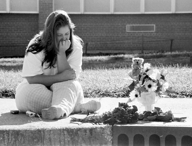 Lori Kauppinen pauses at a sidewalk makeshift memorial Saturday, where friend Anne Coleman was killed Friday, Sept. 21, 2001. Coleman was struck by a car while crossing Douglas Drive on her bicycle. {quote}It couldn't of happened to a nicer person. She was beautiful, funny, so young and full of life,{quote} said Kauppinen.