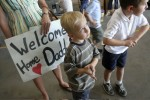 Mark Grismanauskas, center, 4, and brother Cole, 6, wait for their father Erik to return from a 17-day search and rescue for Hurricane Katrina victims in Louisiana. Family members waited with signs and gifts at the FEMA program office Friday, Sept. 16, 2005, in Las Vegas.