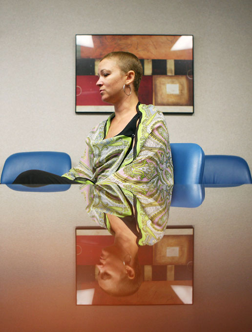 Kristina Lazarus, 41, is reflected onto a table in a conference room at Comprehensive Cancer Center while speaking about her family's experience with cancer. Lazarus has undergone genetic testing for a mutation associated with breast cancer because of her family history with the disease. She recently underwent a double mastectomy as part of treatment for breast cancer.