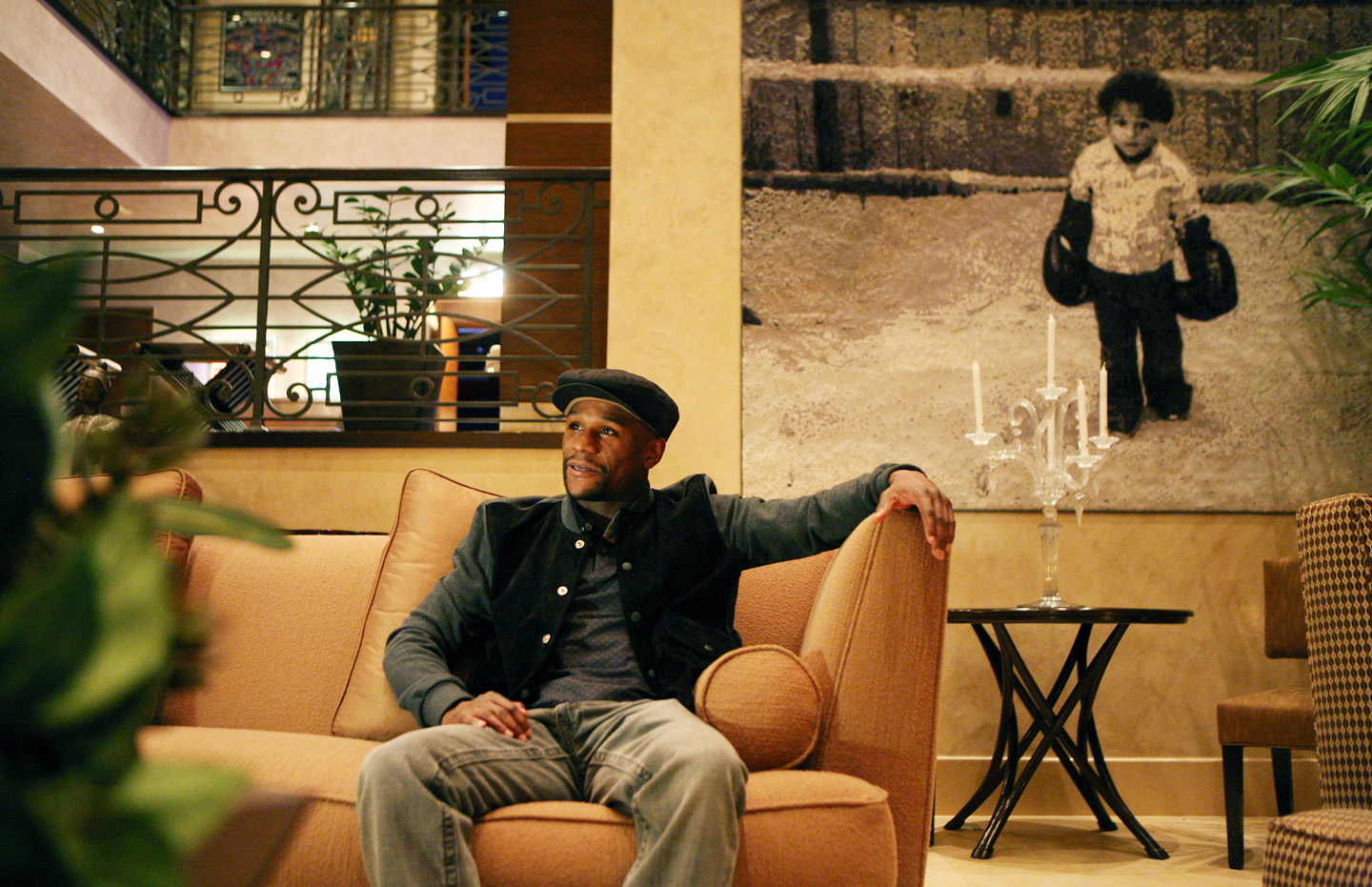 Boxing great Floyd Mayweather sits near a portrait of himself as a child in his Las Vegas home.