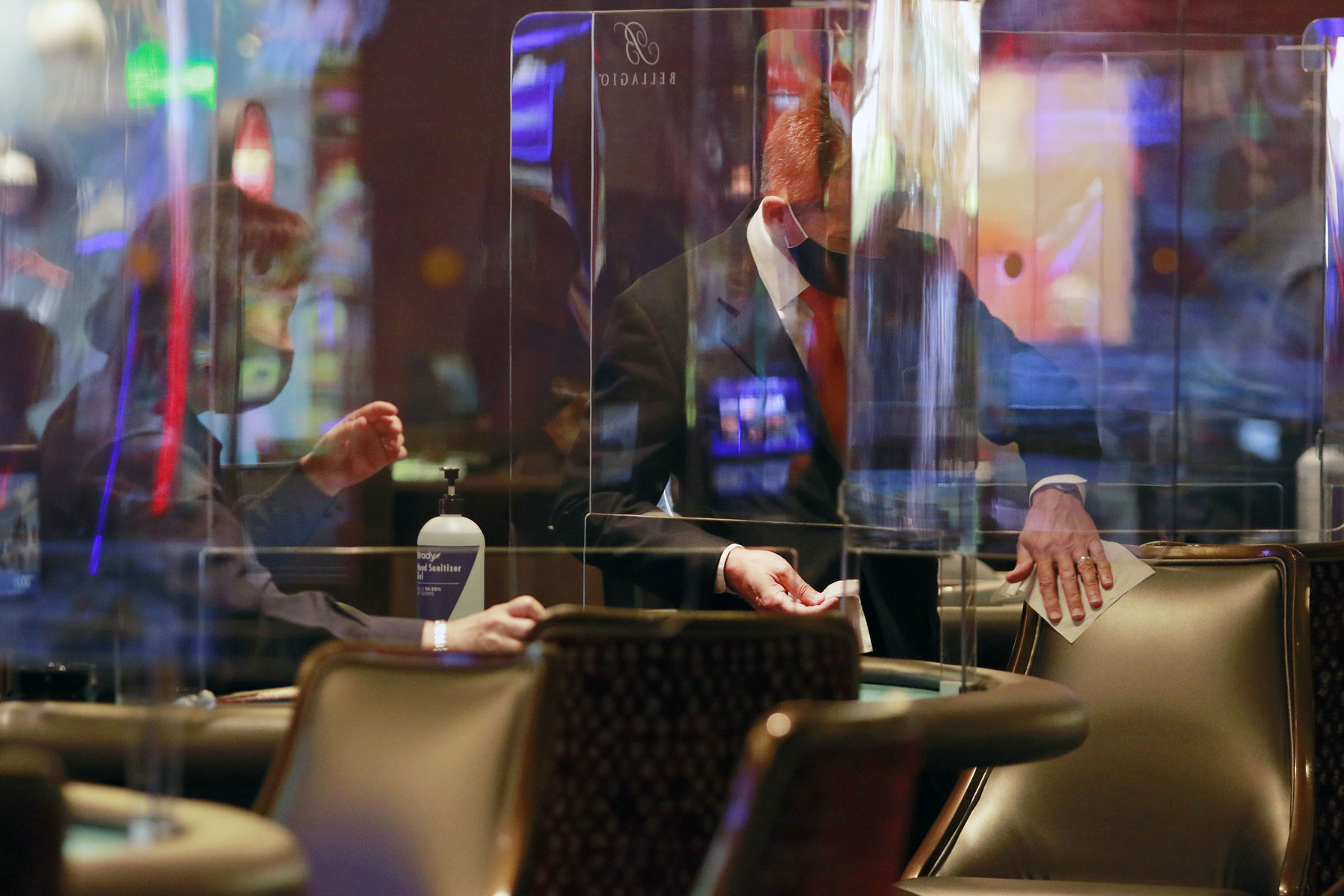 Staff sanitize a table game area between game play at the reopening of Bellagio hotel-casino Thursday, June 4, 2020, in Las Vegas. (Photo by Ronda Churchill/AFP)