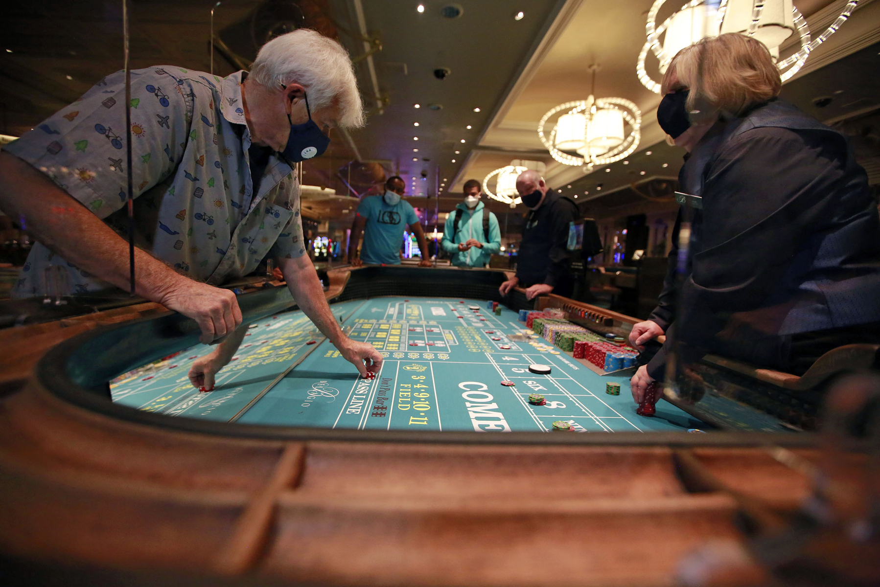 Gene Koonce (cq), left, of Drake, Colorado, plays craps at the reopening of Bellagio hotel-casino Thursday, June 4, 2020, in Las Vegas. (Photo by Ronda Churchill/AFP)