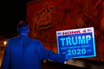 Andy Danevicius holds a sign in the street behind a parked police car that illuminates him blue and joins other Donald Trump supporters in protesting the Nevada vote outside Clark County Election Department Thursday, November 5, 2020, in North Las Vegas. Danevicius, who hails from Canada, said that he became a US Citizen last year to be able to vote in this election. (Photo by Ronda Churchill/AFP)