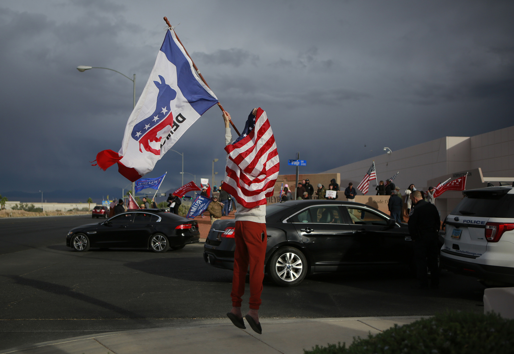 Kevin Abrahami jumps up and down as he waves a Democrat flag when a car passes with passengers showing solidarity with him at Clark County Election Department November 7, 2020, in North Las Vegas. Donald Trump supporters rally across the street from Abrahami.