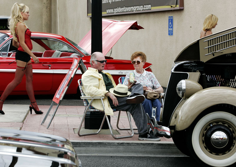 Bill Wright and his mother, Joan, socialize next to his 1936 Ford coupe at the Super Run Car Show on Water Street in Henderson, Nevada.  Behind them, a model walks by a 1961 candy apple red Chevrolet.