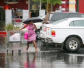 Charell Star jumps over a puddle while making her way back to her car in the rain at Fry's Electronics Friday, July 13, 2012.