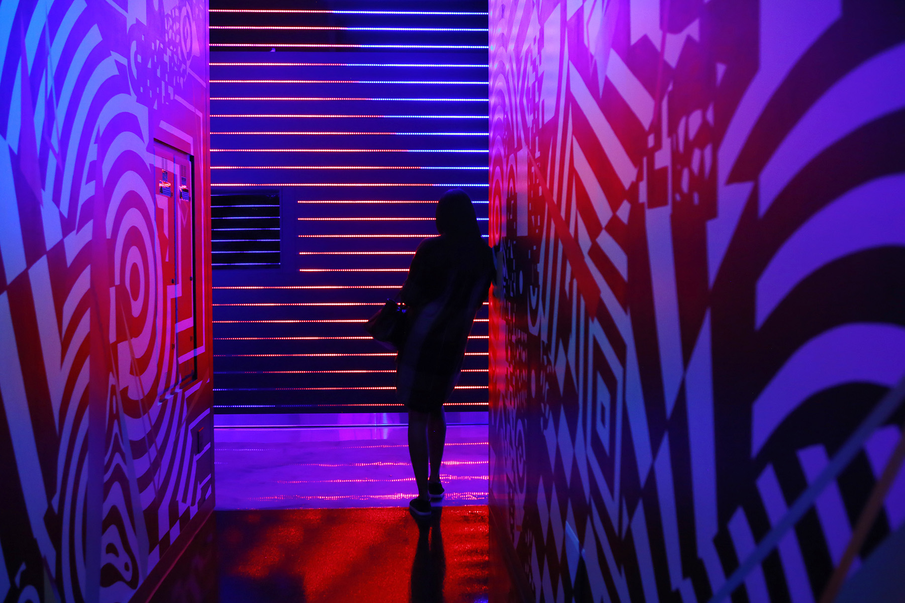 Roqui Theus leans against a wall during an interactive art exhibit on opening day at Meow Wolf's Omega Mart. The interactive art space is Meow Wolf's second permanent installation.