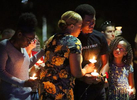 Veronica Hartfield, center, wife of slain LVMPD Officer Charleston Hartfield embraces son Ayzayah Hartfield as daughter Savannah Hartfield, right, looks up during a candlelight vigil. Hartfield was killed Sunday night when a gunman opened fire on the three-day Route 91 Harvest country music festival, leaving 58 dead and over 500 injured in Las Vegas on October 1, 2017.
