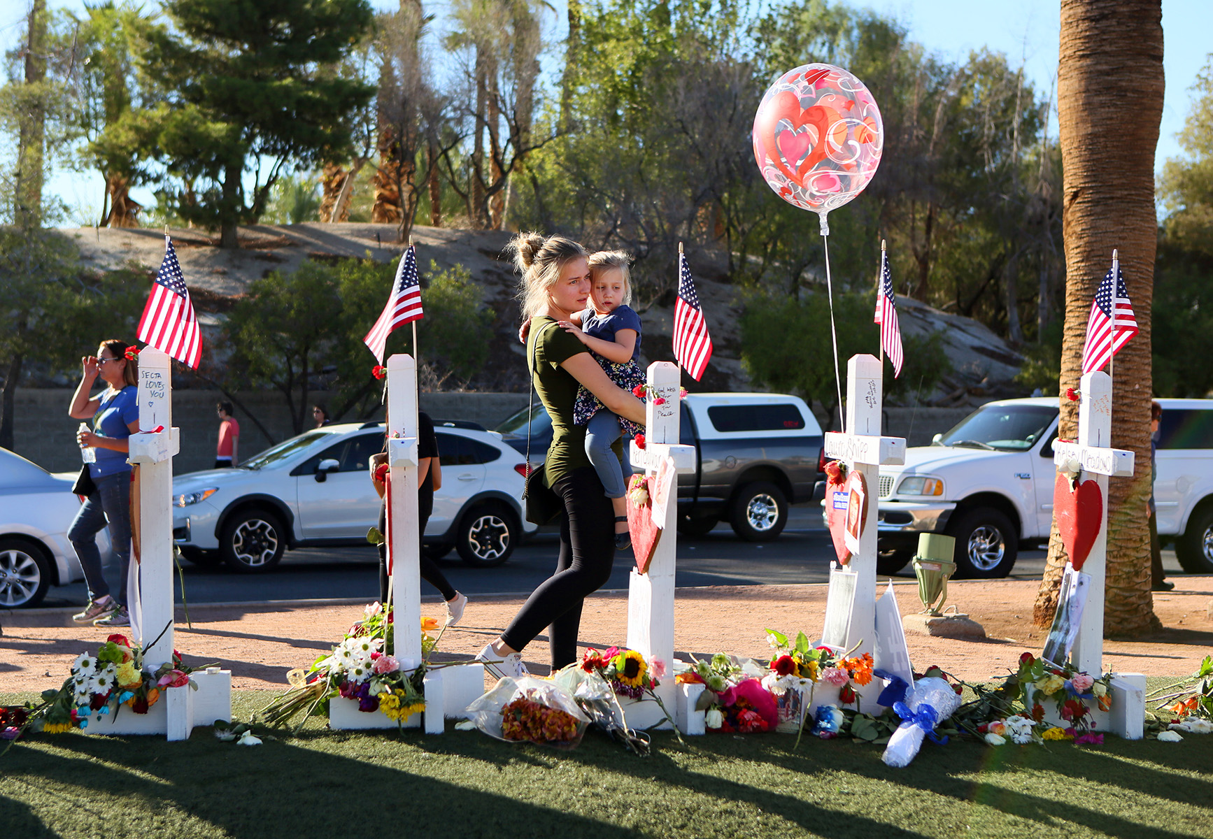 Kaitlyn Proa, center, walks with Aubrey Culbertson, 4, as they pay their respects for the slain victims of the Route 91 Harvest music festival mass shooting at a memorial erected on Las Vegas Boulevard next to the historic Welcome to Las Vegas sign.
