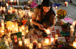Dashenka, Giraldo, lights candles for the victims of Sunday night's Route 91 Harvest mass shooting at a makeshift memorial on the corner of Las Vegas Boulevard and Sahara Avenue Wednesday, Oct. 4, 2017.