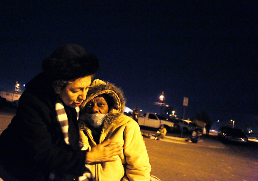 Volunteer Liestela Lee, left, hugs Kathy Washington under a streetlight during a feed the homeless and needy gathering on the corner of McWilliams Avenue and G Street Monday, Nov. 25, 2013, in Las Vegas. Washington suffers from bone cancer and could not to eat. She was there to visit a priest. Different squadrons at Nellis Air Force base, community members, and special interest groups gathered to feed those in need.