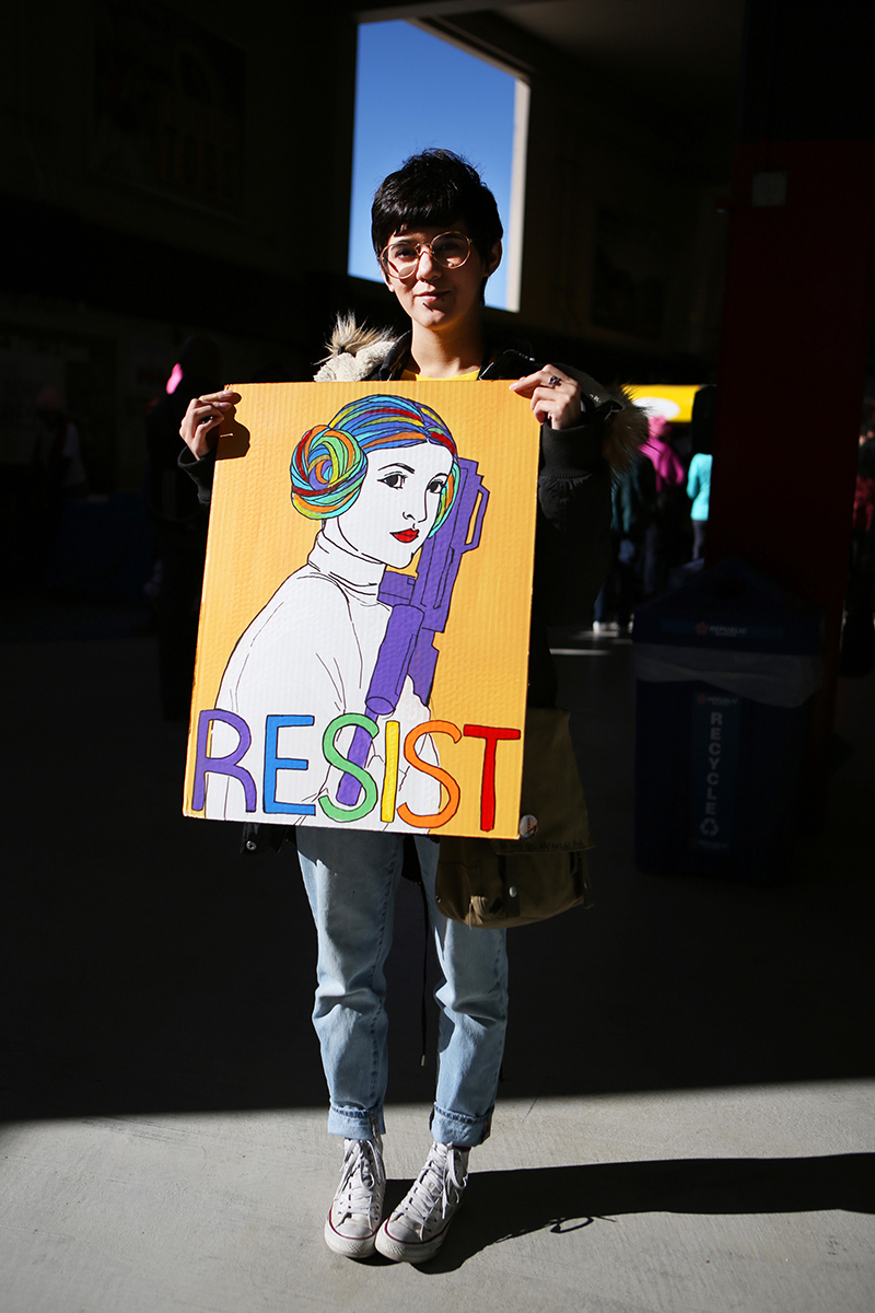 Li G., last name withheld, stands for a photo at a Women's March rally.