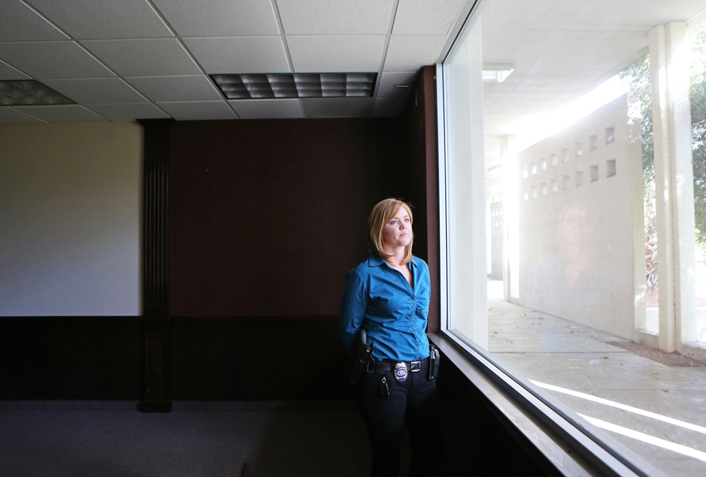 Chrissie Coon, public information officer for North Las Vegas Police Department, looks out the window in what would have been the mayor's office in the former North Las Vegas City Hall Thursday, March 13, 2014, in North Las Vegas. The property, which resides on a 30-acre campus and has 29,000 square feet of contiguous office space, is for sale and was appraised at $3.1 million last November.