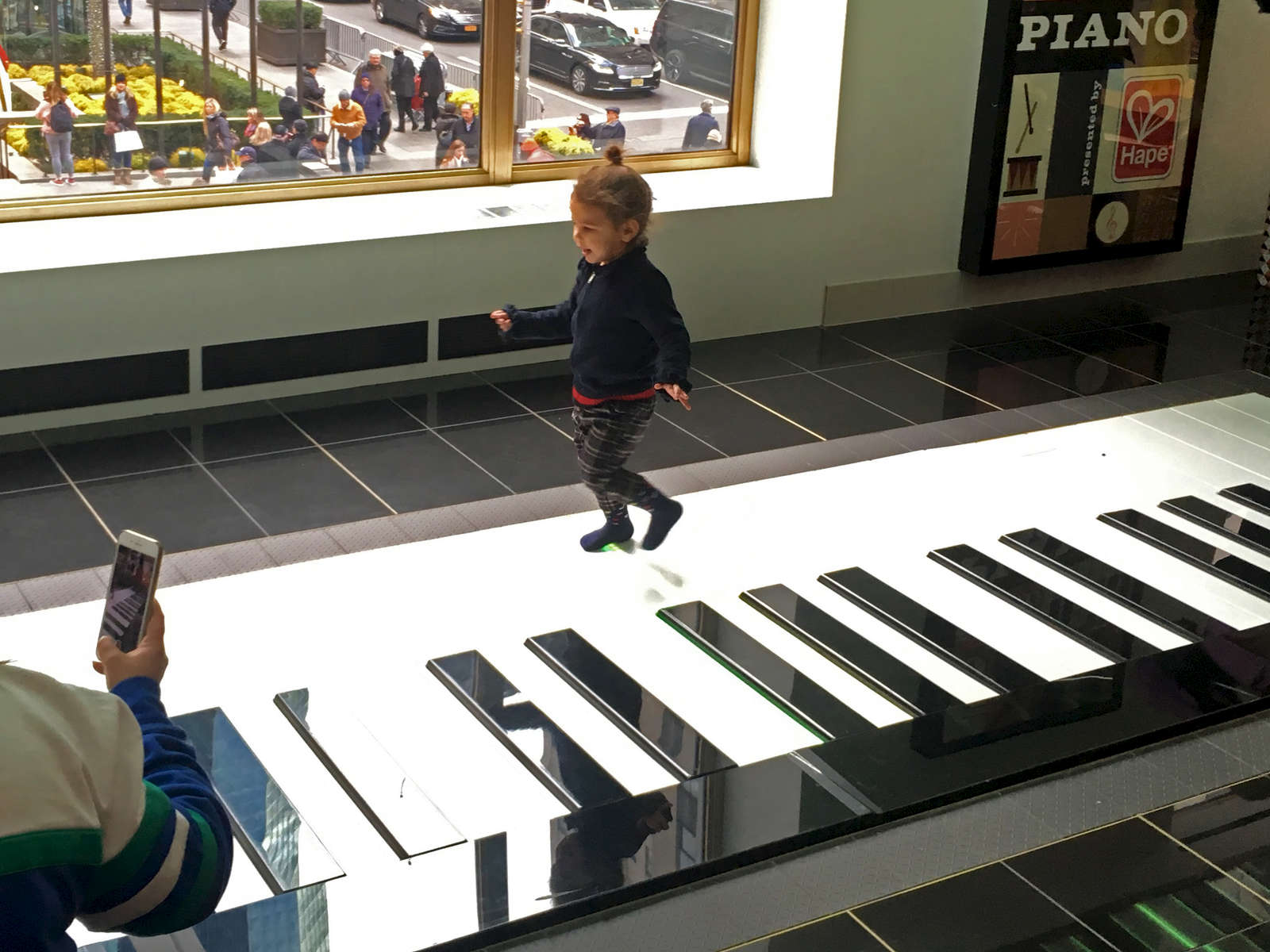 Young girl walks on over-sized piano, FAO Schwartz, NYC. Jon Chase photo