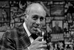 Surrounded by basketball photos spanning four decades, Boston Celtics president Red Auerbach lights up one of his trademark {quote}victory{quote} cigars.