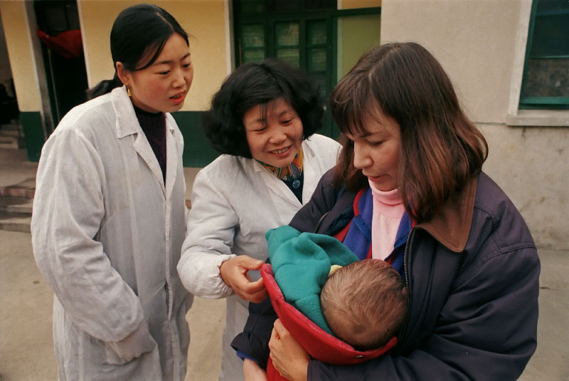 The 7-month-old child of a new adoptive parent is admired by orphanage workers at the Children's Welfare Institute in Hefei.