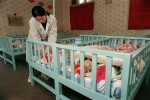 A nurse cares for babies, two to four in a crib, at the Children's Welfare Institute in Hefei, Anhui Province.