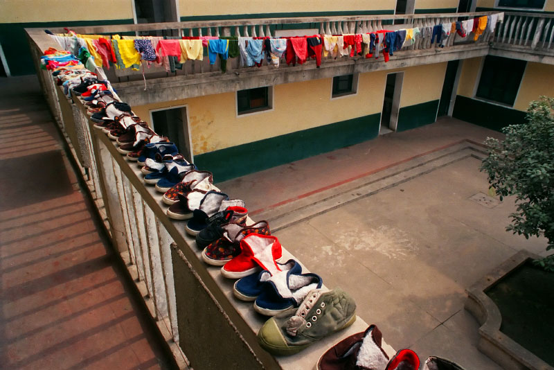 Children's shoes line the balcony as they dry in the sun, at the Children's Welfare Institute in Hefei.