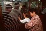 Adoptive parents wait behind a window to receive their child, in the arms of an adoption worker.
