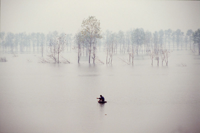 Solitary man fishing from innertube in flooded field, Hubei province, China.