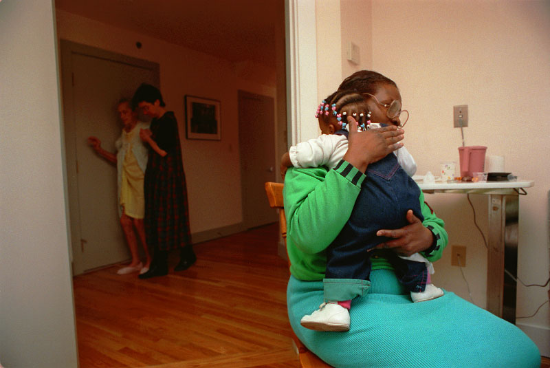 The young child of a patient with AIDS is comforted by an aide.