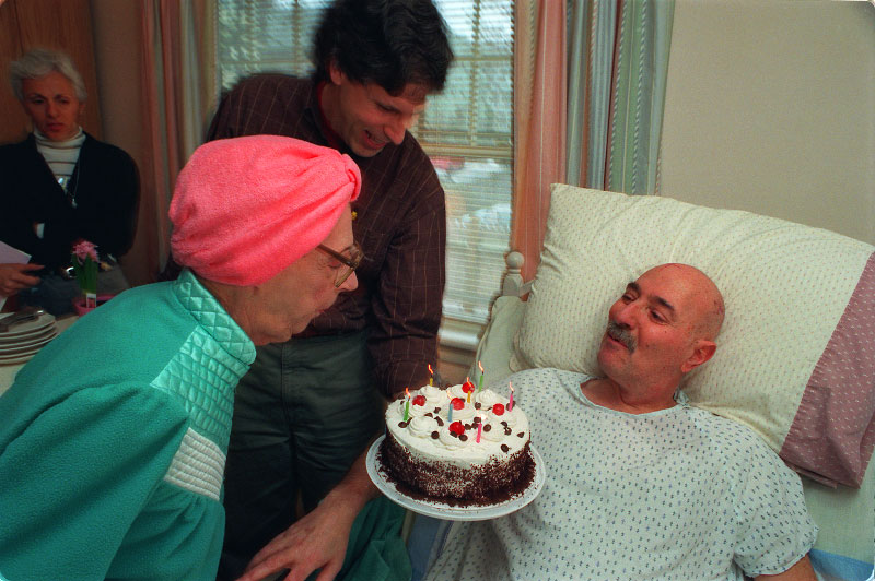 A resident presents a cake to a fellow resident on his birthday, one of many he has celebrated since being told he had only six months to live.