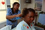 Reginale, a Haitian AIDS patient and mother, has her hair done by the sister of another Haitian patient down the hall.