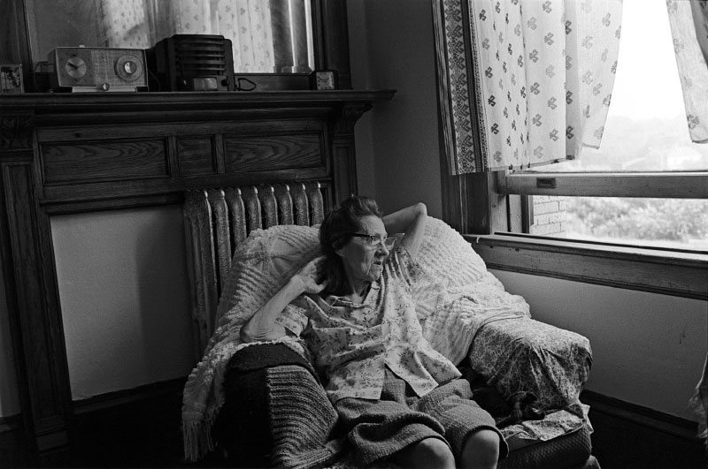 Susan Beamish in her apartment.Those most affected by Druker's development, the people of the Nonantum Block, were outraged. Despite the promise of federal relocation money, residential tenants would have to find housing for an estimated two years of construction, then compete with other Boston area residents for the high-rise subsidized apartments. And whether they returned to Newton Corner or not, their neighborhod would be destroyed.For commercial tenants the outlook was also bleak. An economic study found that rents in the new building would escalate four to six times over current rates, and few, if any, of the existing businesses could afford to return. The message to local merchants was clear: corner stores like Mac's Smoke Shop and Bobby's Fruit were not the kind of upscale businesses envisioned for a revitalized Newton Corner.