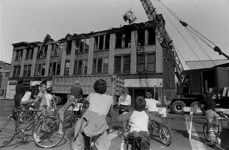Kids watch demolition of one of the five buildings at Newton Corner, after a suspicious fire gutted the vacated structure over Labor Day weekend.{quote}I still get so emotional, after all these years, that I really don't like to talk about this. What bothers me about the fire and makes me sick to my stomach, was the reaction of people watching. It was so crowded and people were so anxious to see the fire, it was like a big show. Everyone was jammed together, just to get near it, and people were yelling, 'Burn! Burn!'{quote}As it burned and the firemen began smashing the windows, people started to applaud. All of a sudden the building looked like it was getting bigger and bigger, like a mountain. Then the windows started to snap. It was like an anger, an out-and-out anger, and the building was in a rage. As huge as the flames were, the building was refusing to go quietly.{quote}Something sacred was being destroyed, and it had to do with the creators of the building, the architects and artists who built it. I had a very glorious, moving feeling as I watched the building burn; it was like seeing a sacred mountain.{quote}Pat Bowles, tenant