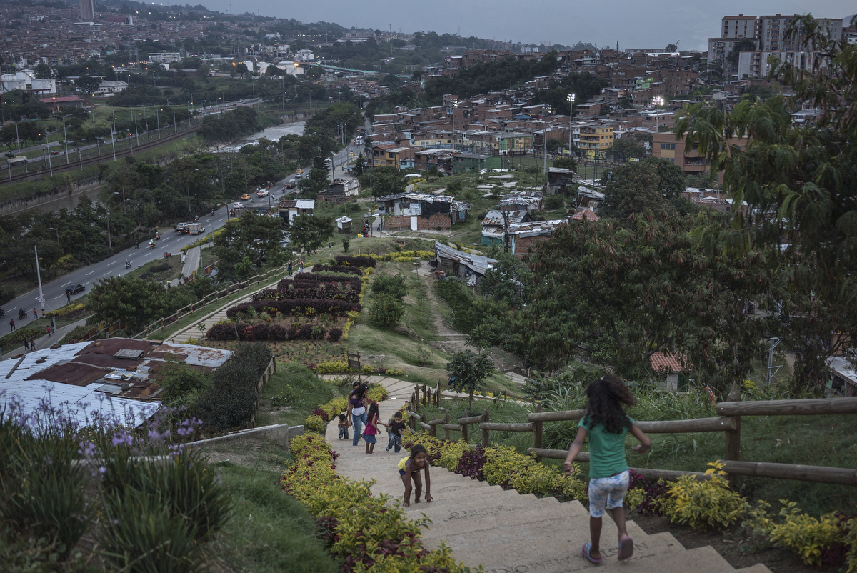 Residents walk the pathway to the top of the {quote}hill{quote}, the area of a new garden. Since 2012, the city of Medellin began an innovative project in the neighbourhood of Moravia to transform the city's main garbage dump into a sustainable garden where 50 thousands residents lived. They did this by planting specific kinds of bacteria and plants to absorb gaseous toxins from the garbage. However to implement the project, the city relocated about 17,000 people Some families moved into high-rise public housing in the community, but others were moved to a remote area of the city, about an hour from their jobs and former neighbourhood.