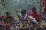 JANUARY 9, 2016 -- Maria Rodrigues, 29, and her husband, Romero Perreira, 39, and their daughter, Veronica, 10, left, visit with Duda, the baby's biological parents who abandoned Duda at the maternity hospital because she couldn't care for their daughter, in their tiny one-room home, in Olinda. Both Maria and her husband, who are recyclers, suffer from a mental disorder and alcoholism.