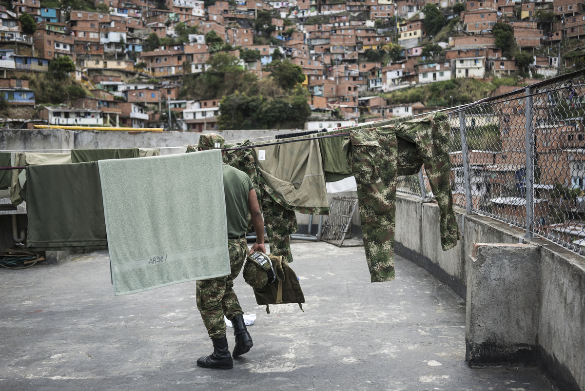 An army unit stationed in Comuna 13, the most dangerous district in Medellin, Colombia. There are eight bases with 140 soldiers in the district. In 2006, the city built a public library, a new school, public green spaces, and improved access to transportation through a cable car line and escalators connecting the neighbourhoods to the metro and the city.