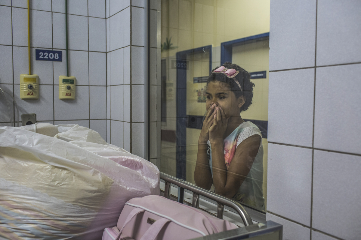 JULY 25, 2016 -- Veronica Pereira, 10, watches her sister, Duda, under the care of Dr. Regina Coeli, director of the children's infectious diseases, at the Oswaldo Cruz University Hospital, in Recife. Duda was hospitalized for a lung infection created by complications with seizures. She hasn't been able to swallow food, so doctors placed a food tube in her.