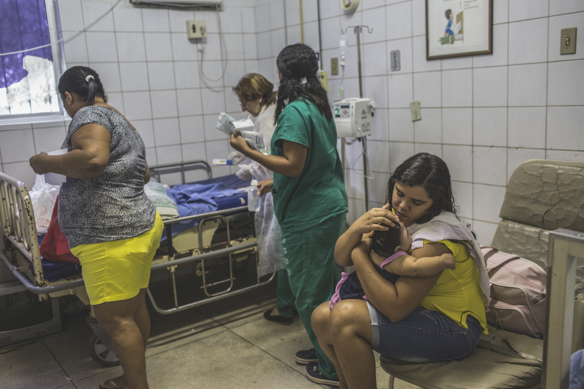 JULY 25, 2016 -- Cleane comforts Duda after doctors remove a feeding tube that bent because it was too large for her, causing discomfort. Duda was hospitalized for a respiratory infection due to her seizures, at Oswaldo Cruz University Hospital in Recife.