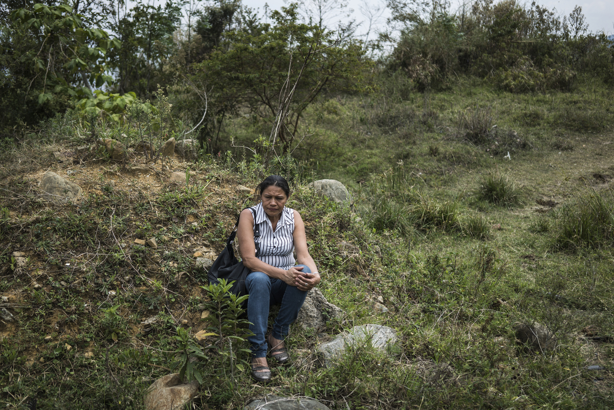 Luz Angela Velasquez waits for the army to return about news of a recent mass grave along a hillside where the city uses to dump construction waste, in Medellin, Colombia. Her son disappeared from a paramilitary that operated in Communa 13, one of the most violent communities in Medellin. Velasquez is part of a group of women who have been fighting for exhumations.