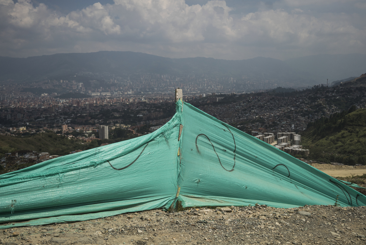 A tarp surrounds a mass grave site that lays untouched for about 10-years as families of the disappeared still await when the government will exhume bodies from the area, near Communa 13, in Medellin, Colombia.