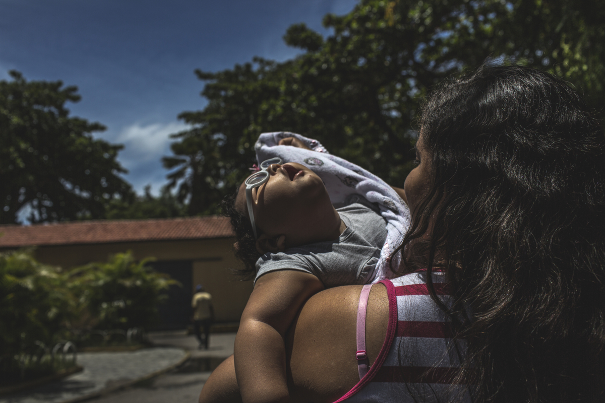 MARCH 15, 2017 -- Although Duda's eyes are sensitive to light and tends to keep her eyes closed, she is mesmerized by its rays and the feeling on her skin, in Recife. Duda has very low vision; she can only see up close and in black and white. Dr. Regina Coeli, director of children's infectious diseases at Oswaldo Cruz University Hospital, said that limited hearing and vision interfere with her development because it is harder for her to be stimulated during the therapies. However, her glasses and hearing aides have helped a lot.