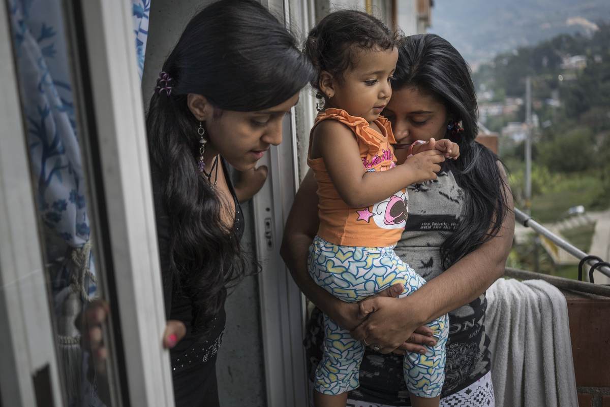 Esica Garcia Acevedo, 32, holding her nice, Kendy Camilo, 2, and her daughter, Francenny Acevedo, 14, left, on their balcony in Nuevo Occidente, a massive social housing complex, of mostly displaced or forced evicted families, in Medellin, Colombia. 18 family members live in a 70 square meter apartment given to them by the city in order to relocate the family from Moravia, a former garbage dump turned garden. The family's world takes place mostly inside their apartment. The children do not play outside because the parents say its too dangerous with speeding motorbikes and bad neighbors. The family says the city promised parks and programs for the children, but it never came. They often miss their old neighborhood.