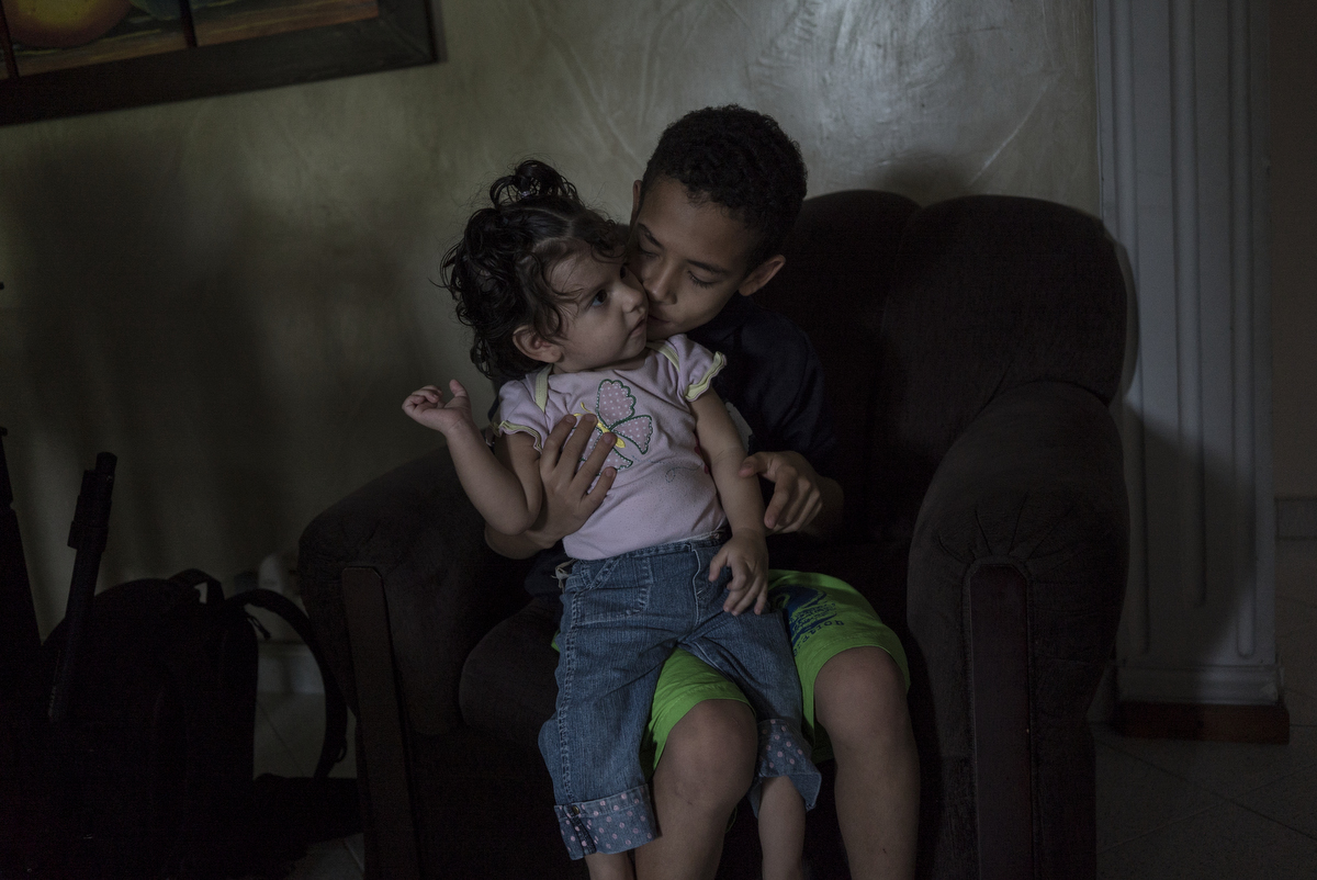 Wilder Gonzalez, 10, holds his baby sister, Katherine, at a family home shelter in a city program called, {quote}Madres Acojientes,{quote} in Medellin, Colombia.