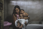 MARCH 15, 2017 -- Cleane carries Duda, who weighs 16kgs, or about 35lbs, from the tub. The family stores clean water in an open container in the bathroom, but they go through the barrel of water fast enough to refill it every week when they receive water. They said the city stopped passing out free bacteria that kills mosquito larvae sometime after January this year.