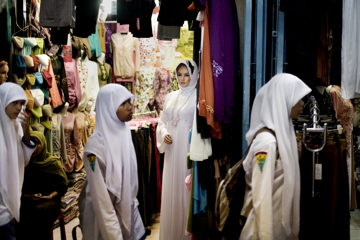 Students walk past a veiled, caucasian looking mannequin in a market in Banda Aceh, Indonesia, Thursday, Nov. 19, 2009. Since the provincial government of Aceh Province implemented a moderate form of sharia law on conduct and dress in Aceh, dozens of Muslim clothing shops opened in the markets and malls.