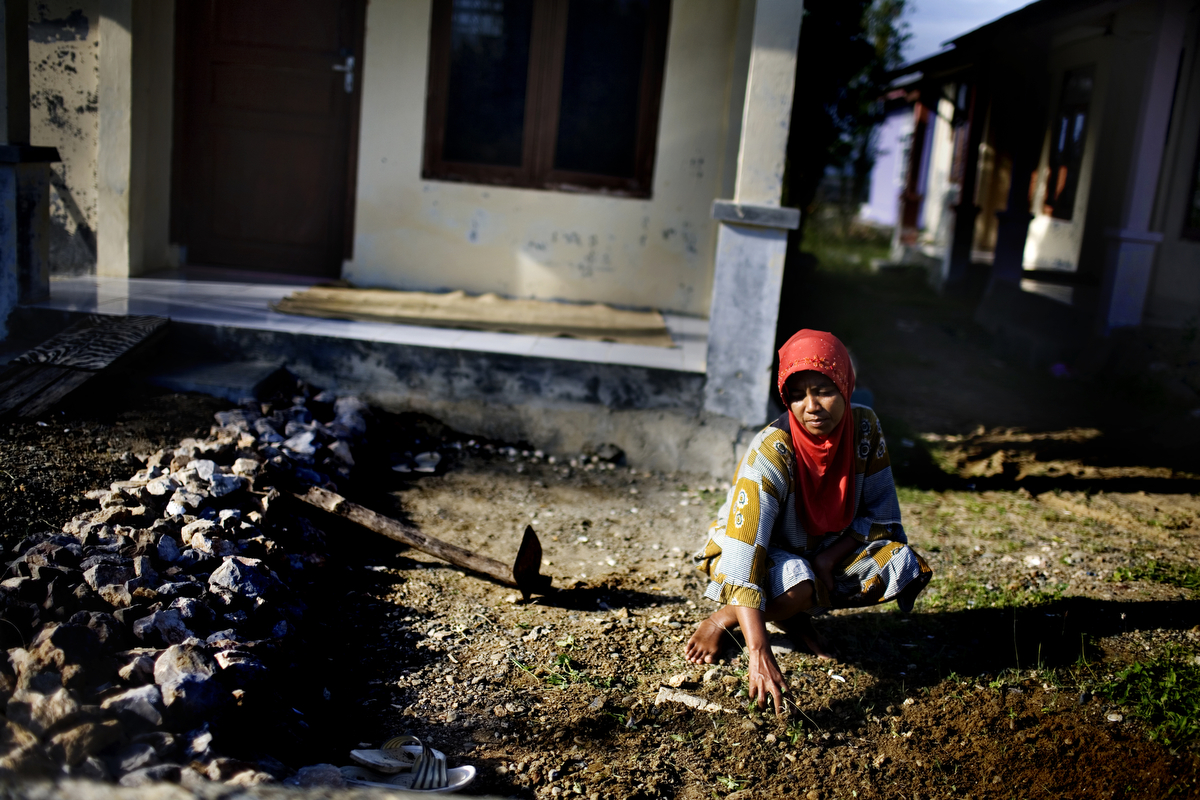 A woman sifts through dirt, pulling weeds in front of her new home which was built by the Irish Red Cross, in Banda Aceh, Indonesia, on Tuesday, Nov. 17, 2009. Although Aceh is a matriarchal culture, women who break Sharia rules are often stigmatized, and often become objects of harassment.