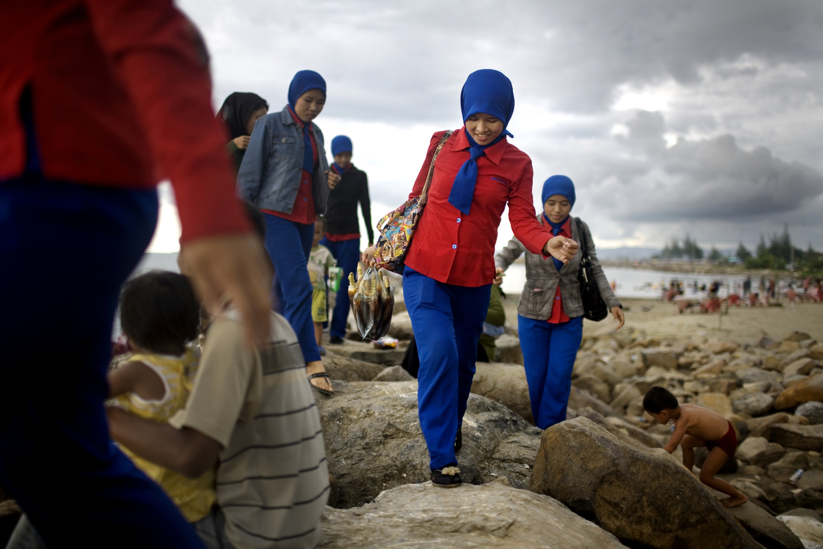 "Acehnese women walk along a new jetty created by the tsunami, in Ulele Beach, outside of Banda Aceh, Indonesia, Sunday, Nov. 8, 2009. Most families head to the beaches on Sundays. Although many Acehnese women embrace Sharia, they don't agree with it. Dozens of women's clothing stores that have opened since the tsunami, offering a colorful selection of veils and stylized Islamic tunics. As Acehnese women friends have confided, ""There is Sharia – but at least there is no war."""