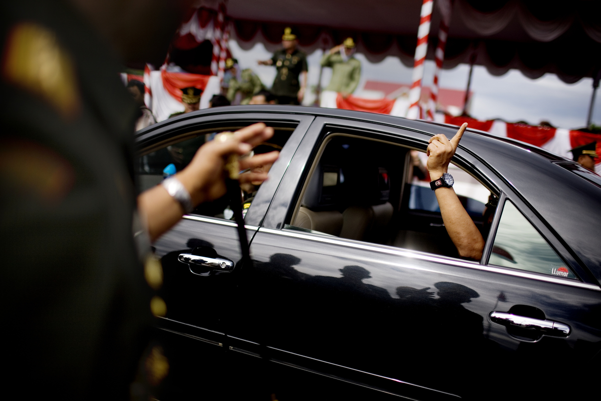 Former Army General Soenarko holds up a {quote}number one{quote} finger out the car window as he departs his post after a general handover event in Banda Aceh, Indonesia, on Nov. 20, 2009. Since the signing of Helsinki peace accord in 2005 that ended the longest conflict in Indonesia between the Free Aceh Movement and Indonesian government, the country has pulled out more then 20,000 troops from the province. The army base in Banda Aceh currently has about 15,000 soldiers.