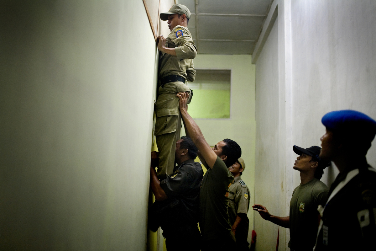 Sharia Police, or the morality police, check out rooms in a brothel in Banda Aceh, Indonesia, on Saturday, Nov. 21, 2009. Banda Aceh enforces a moderate form of Islamic Law.  In 2003, the provincial government of Aceh Province implemented a moderate form of sharia law on conduct and dress in their effort to reclaim Aceh as the Islamic capital of SE Asia.  Although Aceh is a matriarchal culture, women who break Sharia rules are often stigmatized, and often become objects of harassment, especially rape. Young adults who admit to having premarital sex are forced into marriage.